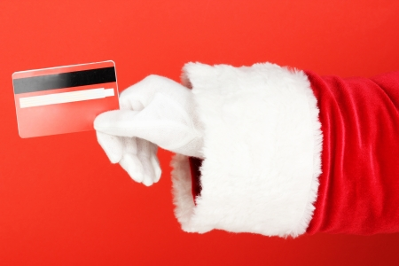 st nick: Santa Claus hand holding red credit card on red background