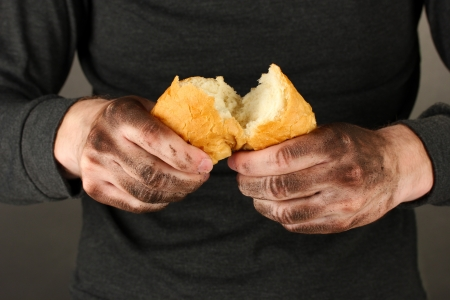 homeless man holding a white bread, close-up Stock Photo - 17000744