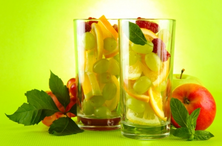 transparent glasses with citrus fruits, on grren background Stock Photo - 17000369