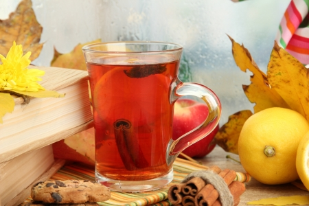 cup of hot tea and autumn leaves, on wooden table photo