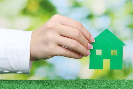 concept: woman hand with paper house on green background, close up Stock Photo - 17000556