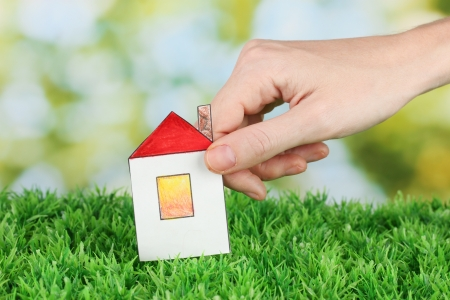 Female hand holding paper house on green background, close up Stock Photo - 17000779