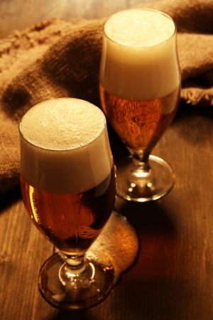 Glasses of beer on wooden table close-up photo