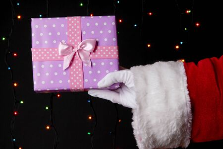 Santa Claus hand holding gift box on bright background Stock Photo - 17000685
