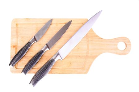 Set of knives on cutting board isolated on white photo
