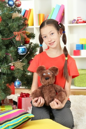 Little girl holding toy near christmas tree photo