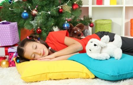 Little girl sleeping near christmas tree Stock Photo - 17186469