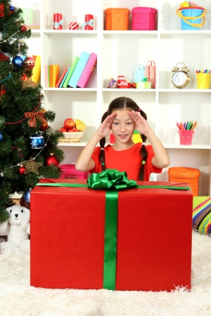 Little girl with large gift box near christmas tree Stock Photo - 17186545
