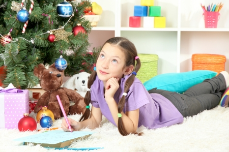 Little girl writing letter to Santa near christmas tree photo
