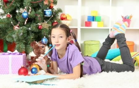 letter box: Little girl writing letter to Santa near christmas tree
