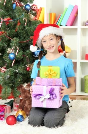 Little girl holding gift boxes near christmas tree Stock Photo - 17129517