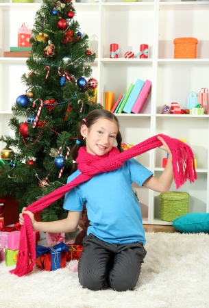 Little girl with pink scarf  sitting near christmas tree photo