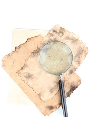 Old paper with magnifying glass isolated on white photo