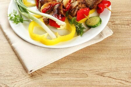 tasty grilled meat and vegetables on skewer on plate, on wooden table photo