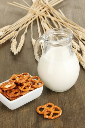 Tasty pretzels in white bowl and milk jug on wooden table close-up Stock Photo - 17000887