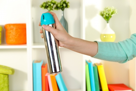 Sprayed air freshener in hand on white shelves background Stock Photo - 17000025