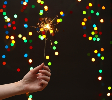 beautiful sparkler in woman hand on garland background