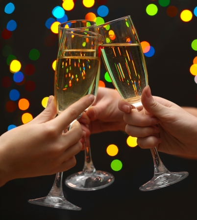 woman hand with glasses of champagne, on garland background  photo