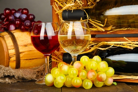 dura: Wooden case with wine bottles, barrel, wineglass and grape on wooden table on grey background