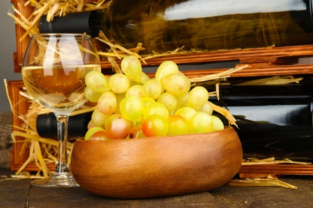 Wooden case with wine bottles, wineglass and grape close up Stock Photo - 17000822
