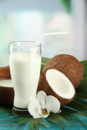 Coconut with glass of milk,  on blue wooden table photo