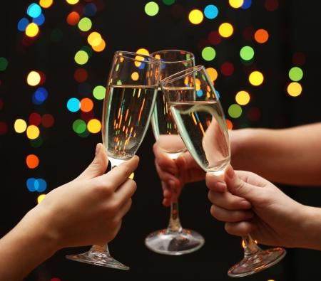 brindisi spumante: mano della donna con bicchieri di champagne, su sfondo ghirlanda
