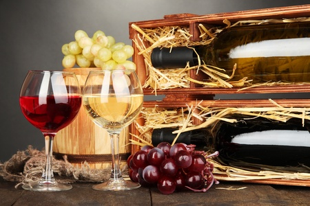Wooden case with wine bottles, barrel, wineglasses and grape on wooden table on grey background photo
