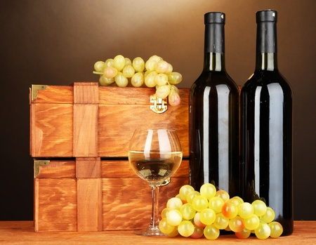 dura: Wooden cases with wine bottles on wooden table on brown background Stock Photo