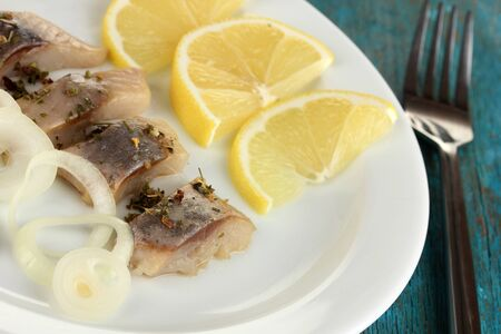 Dish of herring on plate on blue wooden table close-up Stock Photo - 17000660