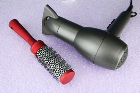 hair dryer and comb brush, on purple background photo