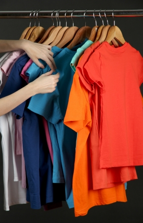Variety of casual shirts on wooden hangers, isolated on black photo