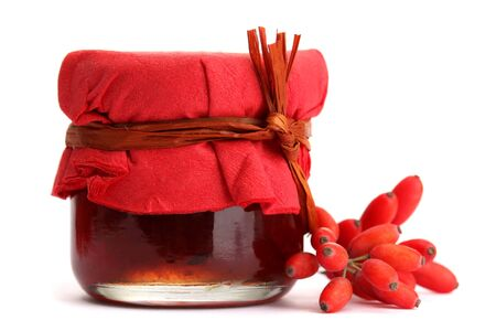 ripe barberries and jar of jam isolated white