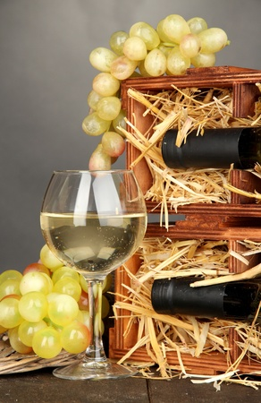 Wooden case with wine bottles, wineglass and grape on wooden table on grey background Stock Photo - 17021556
