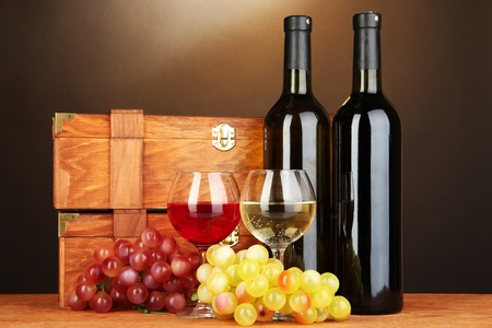 Wooden cases with wine bottles on wooden table on brown background Stock Photo - 17021628