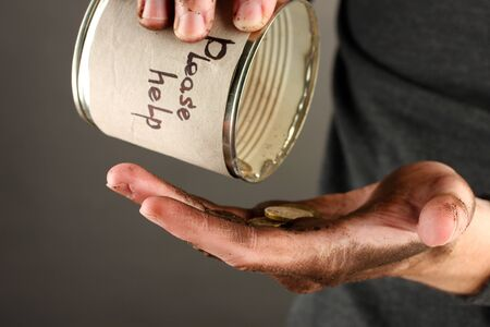 waif: homeless pours money from bank, close-up Stock Photo