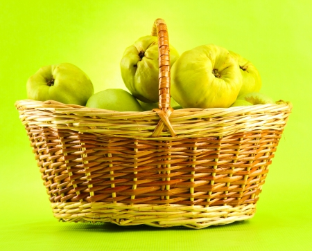 quinces: sweet quinces in basket, on green background
