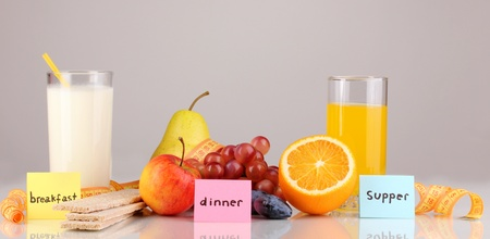 Dietary foods for breakfast, dinner and supper on grey background photo