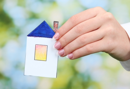 concept: woman hand with paper house on green background, close up Stock Photo - 17046981
