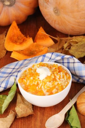 Useful pumpkin porridge in white plate on wooden table close-up photo