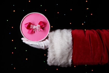 Santa Claus hand holding gift box on bright background Stock Photo - 17047233