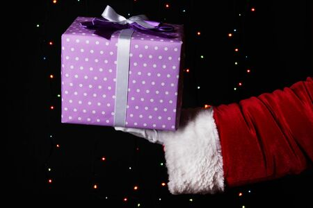Santa Claus hand holding gift box on bright background Stock Photo - 17047276