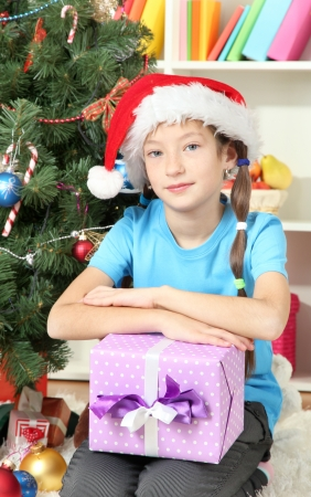 Little girl holding gift box near christmas tree Stock Photo - 17186477