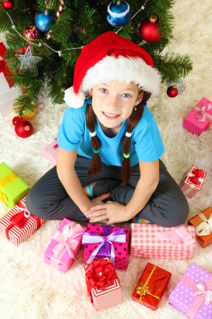 Little girl  sitting near christmas tree photo