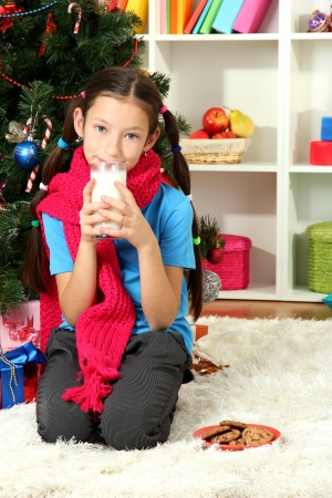 Little girl with pink scarf and glass of milk sitting near christmas tree Stock Photo - 17186449