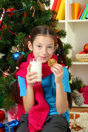 Little girl with pink scarf and glass of milk sitting near christmas tree Stock Photo - 17186444