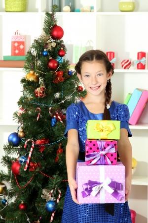 Little girl holding gift box near christmas tree Stock Photo - 17129491