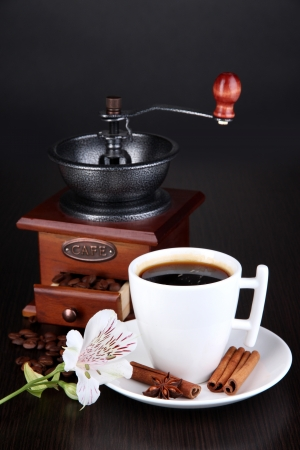 Cup of coffee with coffee mill on wooden table photo