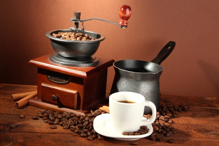 coffee pot: Coffee grinder, turk and cup of coffee on brown background Stock Photo