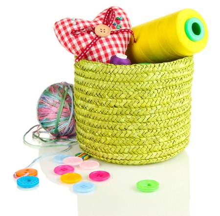Green wicker basket with accessories for needlework isolated on white photo
