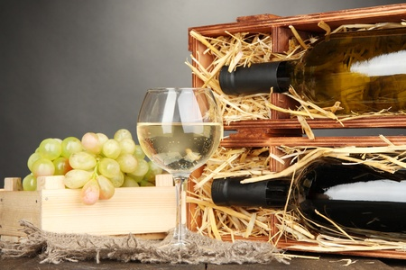 cabarnet: Wooden case with wine bottles, wineglass and grape on wooden table on grey background Stock Photo